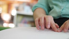 Close-up of disability blind person woman hands moving fingers reading Braille book studying in creative library. Braille is a