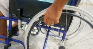 Close-up of disabled active senior African American man moving his wheelchair on promenade 4k. Close-up of disabled active senior African American man moving his stock video footage