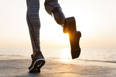 Close up of disabled athlete woman with prosthetic leg. Running outdoor at the beach stock photos