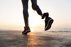 Close up of disabled woman with prosthetic leg. Running outdoor at the beach royalty free stock photos