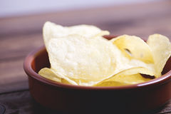 Close-up of a dish with chips standing on dark gray colored wooden table. Royalty Free Stock Images