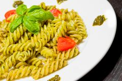 Close-up of dish of pasta with pesto genovese sauce and vegetables, tomato and basil Royalty Free Stock Image