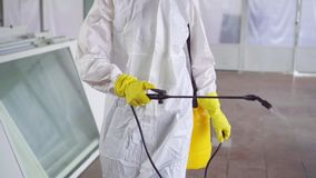 Close up disinfector in special clothes sprays pesticides in the warehouse