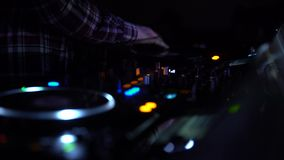 Close-up of disk jockey hands mixing music records, nightclub atmosphere
