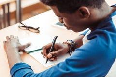 close-up disparado da escrita afro-americano do estudante imagens de stock