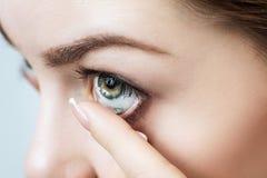 Close-up disparado da lente de contato vestindo da jovem mulher fotografia de stock royalty free