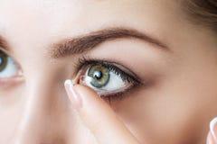 Close-up disparado da lente de contato vestindo da jovem mulher imagem de stock