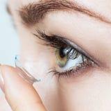 Close-up disparado da lente de contato vestindo da jovem mulher imagens de stock