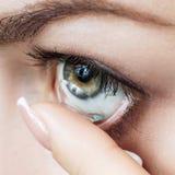 Close-up disparado da lente de contato vestindo da jovem mulher imagem de stock royalty free