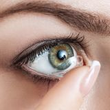 Close-up disparado da lente de contato vestindo da jovem mulher fotografia de stock