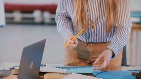 Close-up disparado da posição bem sucedida da mulher de negócios atrás da tabela do escritório na reunião da equipe do negócio, d filme