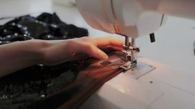 Close up disparado das mãos fêmeas que trabalham na máquina de costura Jovem mulher que usa uma máquina de costura em casa ou na  video estoque