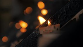 Close-up disparado de muitas velas ardentes na igreja Católica com o fundo blured escuro vídeos de arquivo