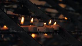 Close-up disparado de muitas velas ardentes na igreja Cat?lica com o fundo blured escuro video estoque