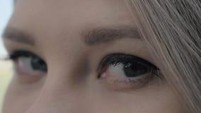 Close-up disparado de uma mulher europeia loura bonita que abre seus olhos cinzentos filme