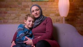Close-up disparado do menino pequeno e sua de mãe muçulmana no hijab que sorriem na câmera que acaricia-se em casa video estoque