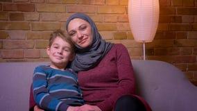 Close-up disparado do menino pequeno e sua de mãe muçulmana no hijab que sorriem na cabeça do declive da câmera entre si em casa video estoque