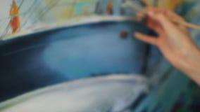 Close-up disparado do pincel fêmea sujo da terra arrendada da mão e de cores de mistura na paleta que pinta então a paisagem mari vídeos de arquivo