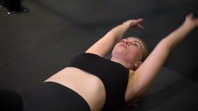Close-up disparado do sportsgirl novo que faz a elevação cruzada do pé e da mão que está sendo concentrada e motivada no gym video estoque