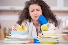 Close up of displeased housewife drying dishes Stock Photo