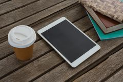 Disposable glass, books and digital tablet on wooden plank Stock Image
