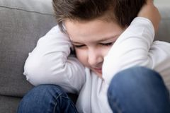 Close up of stressed child cover head suffering from conflicts. Close up of distressed little boy cover head suffer from family home conflicts or domestic royalty free stock image