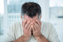 Close-up of a distressed man. Distressed man covering his face in front of window Royalty Free Stock Images