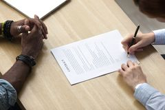 Diverse business people signing legal document on desk royalty free stock images