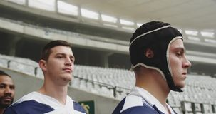 Male rugby players standing in the stadium 4k. Close-up of diverse male rugby players standing in the stadium. They are looking away 4k stock footage