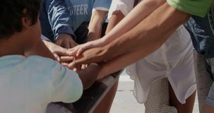 Volunteers forming hand stack on the beach 4k. Close-up of diverse volunteers forming hand stack on the beach. They are smiling 4k stock video footage