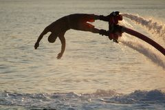 Close-up of diving Flyboarder backlit against waves Royalty Free Stock Photography