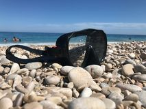 Close-up of a diving mask on the stones of a beach stock image