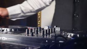 Close up of DJ hands playing party music on modern cd usb player in disco club - Nightlife and entertainment concept. DJ. Turntable console mixer controlling stock footage