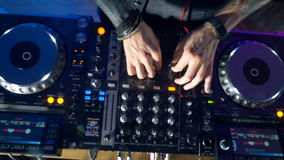 Close-up of a dj hands using mixer and turntables in nightclub. stock video