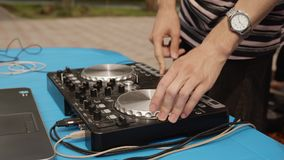 Close up DJ mixing music on sound console at outdoor party. Disc jockey playing music on controller panel. Mixing deck