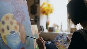Close-up do artista da mulher que pinta ainda a imagem da vida na lona no estúdio da arte Imagens de Stock