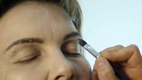 Close-up do artista de composição profissional que aplica o lápis de olho na pálpebra O estilista está fazendo compensa pela fême video estoque