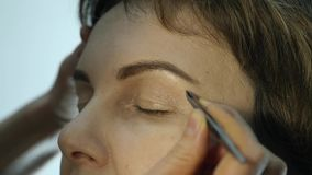 Close-up do artista de composição profissional que aplica o lápis de olho na pálpebra O estilista está fazendo compensa pela fême filme