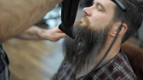 Close-up do barbeiro que faz que denomina com um homem considerável com uma barba longa Mãos do ` s do cabeleireiro no processo d vídeos de arquivo