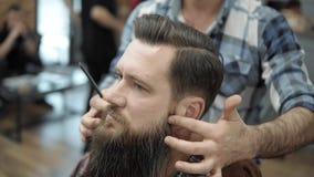 Close-up do barbeiro que faz que denomina com um homem considerável com uma barba longa Mãos do ` s do cabeleireiro no processo d filme