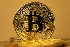 Close up do bitcoin brilhante do ouro no backgound amarelo fotos de stock
