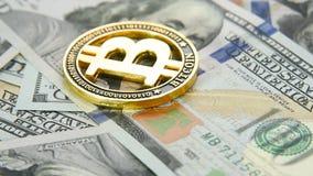 Close-up do bitcoin da moeda de ouro no fundo de cem notas de dólar de dólares americanos rotação filme