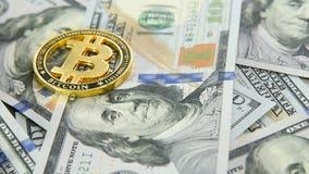 Close-up do bitcoin da moeda de ouro no fundo de cem notas de dólar de dólares americanos rotação vídeos de arquivo
