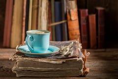 Close up do bolo de queijo caseiro e do café no livro na biblioteca imagens de stock royalty free