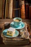 Close up do bolo de queijo e do café rústicos no livro na biblioteca foto de stock