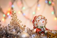 Close-up do boneco de neve no fundo do ouropel colorido obscuro das luzes e do ano novo feliz fotografia de stock royalty free