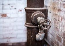 Close up do botão no torneira e na tubulação velhos imagem de stock