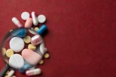 Close up do branco e da cor pils e cápsulas no fundo vermelho Fundo médico imagens de stock