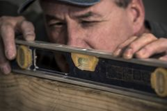Close up do carpinteiro masculino que usa a ferramenta nivelada na placa de madeira foto de stock