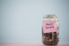 Close-up do cartão e da fita cor-de-rosa da conscientização do câncer da mama no frasco com as moedas na tabela Fotografia de Stock